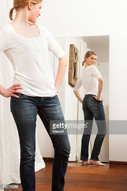 Woman checking her body in the mirror.
