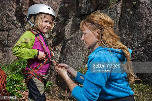 Woman checking  her daughters  equipment before climbing