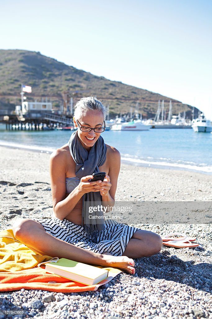 Woman checking her phone on the beach : Stock Photo
