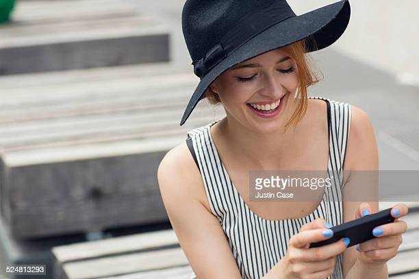 woman checking her phone while sitting outside