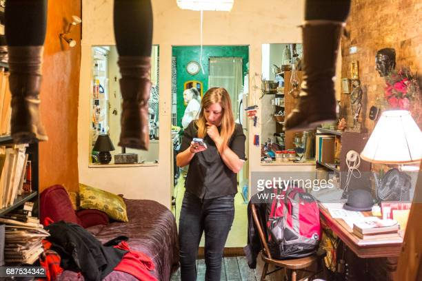 Woman checking her smart phone in a cramped small eclectic apartment in New York City USA