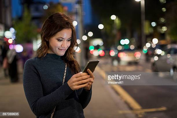 Woman checking her smartphone by the roadside