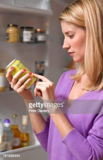 Woman checking ingredients on can