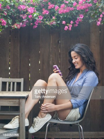 Woman checking mobile device in back yard : Stock Photo