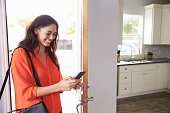 Woman Checking Mobile Phone As She Opens Door Of Apartment