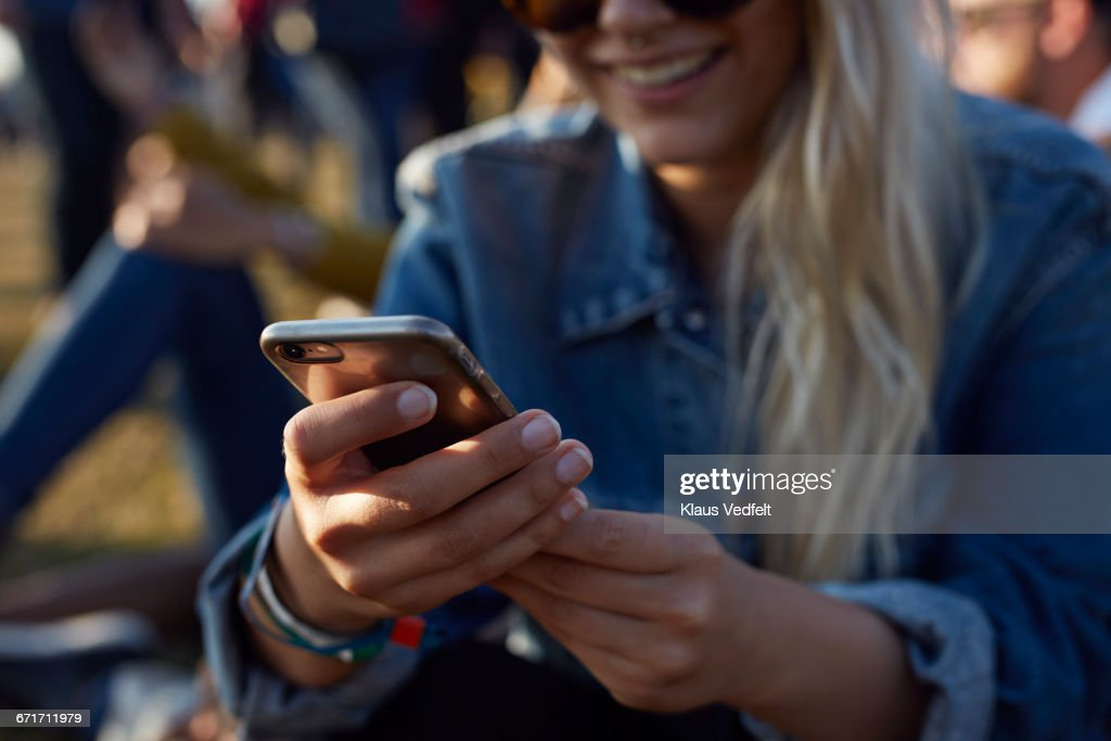 Woman checking phone at festival : Stock Photo