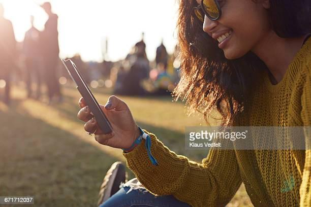 Woman checking phone at festival