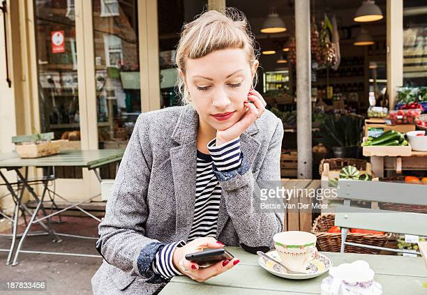 Woman checking phone at outdoor cafe farm shop.