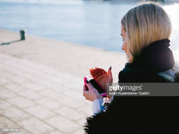 Woman Checking Phone On Promenade