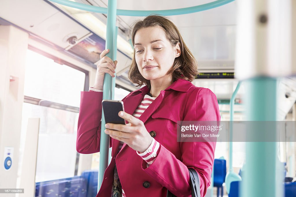 Woman checking phone while standing in train : Stock Photo