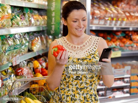 Woman checking shopping list on mobil phone : Stock Photo