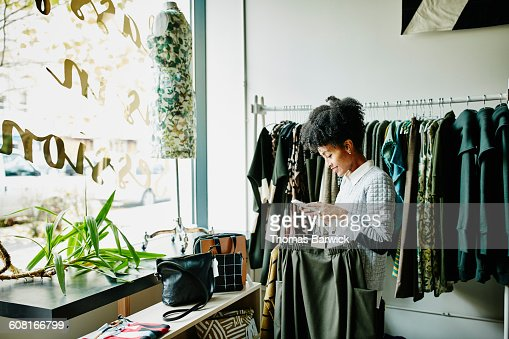 Woman checking smartphone while shopping