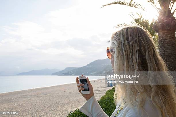Woman checking text message on smart phone, beach