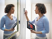 Woman checking thermostat with energy tracking application on digital tablet