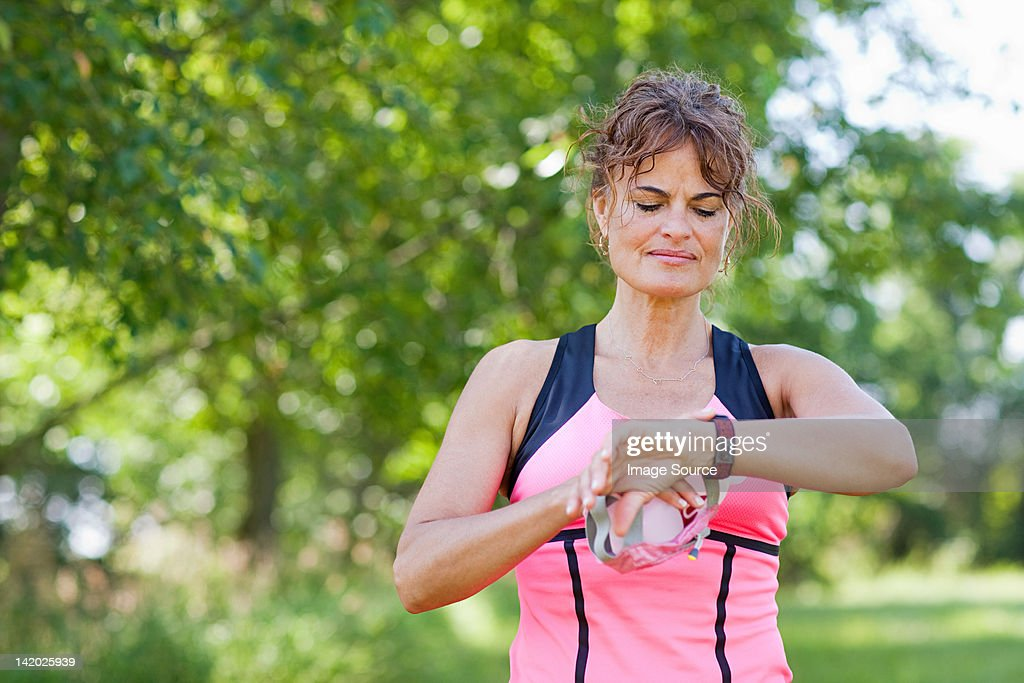 Woman checking watch during exercise : Stock Photo