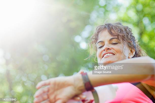Woman checking watch during exercise