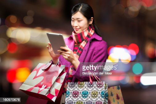 Woman checking wireless device in city,
