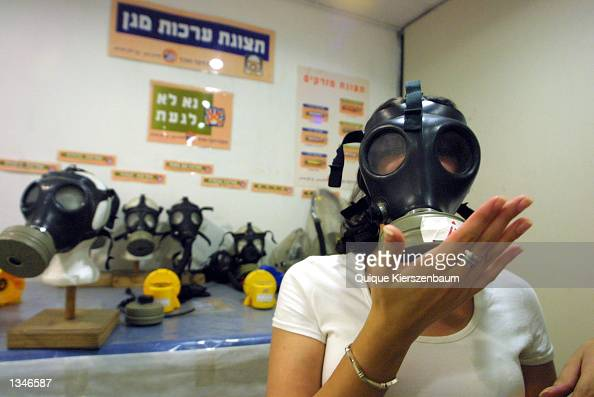 A woman checks a gas mask at a distribution center in a shopping mall August 21 2002 in Jerusalem Israel Citizens and soldiers are preparing for the...