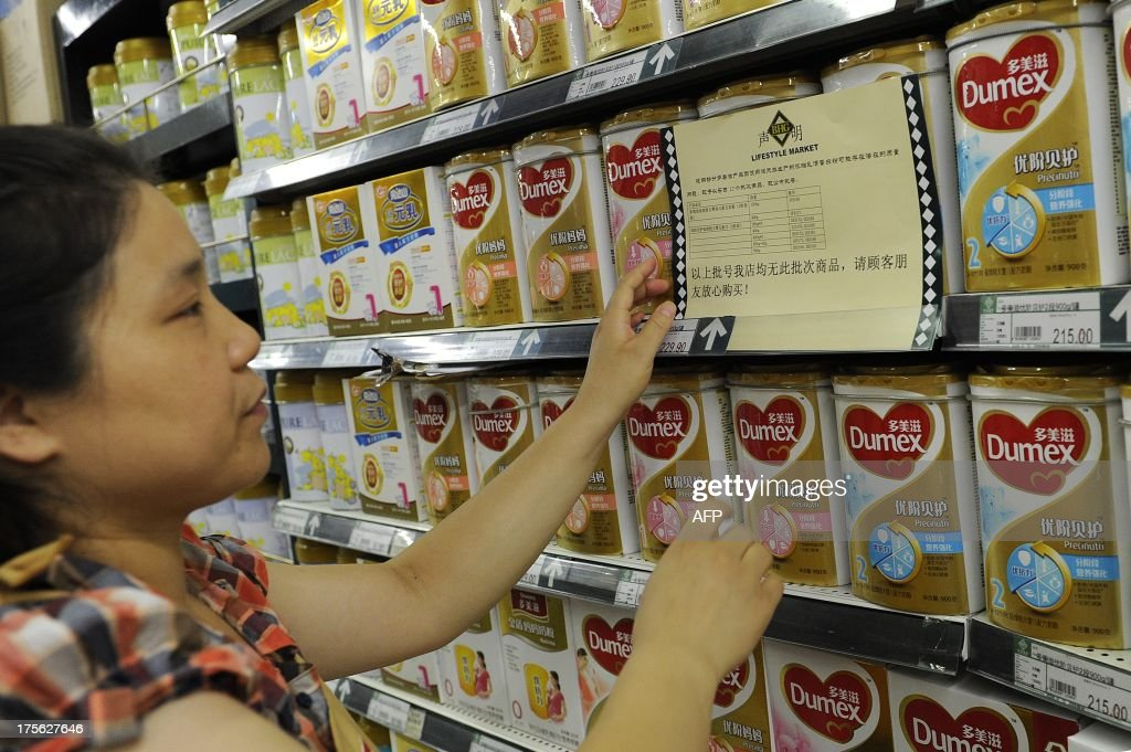 A woman checks a guarantee announcement on a shelf of Dumex baby formula, which uses the New Zealand dairy Fonterra as its raw material supplier, at a supermarket in Hefei, north China's Anhui province, on August 5, 2013. China stepped up warnings to consumers on August 5 over a botulism scare involving products from the New Zealand dairy company Fonterra, and has demanded affected importers check their sales records. CHINA OUT AFP PHOTO