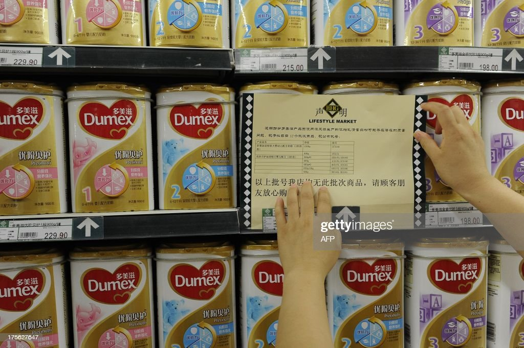A woman checks a guarantee announcement on a shelf of Dumex baby formula, which uses the New Zealand dairy Fonterra as its raw material supplier, at a supermarket in Hefei, north China's Anhui province, on August 5, 2013. China stepped up warnings to consumers on August 5 over a botulism scare involving products from the New Zealand dairy company Fonterra, and has demanded affected importers check their sales records. CHINA