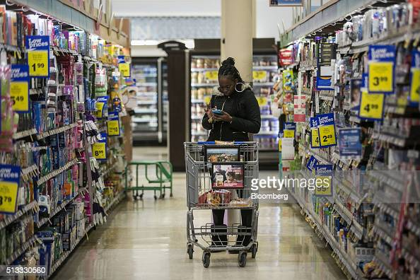 A woman checks a mobile phone while shopping at a Kroger Co grocery store in Birmingham Michigan US on Tuesday March 1 2016 Kroger Co is scheduled to...