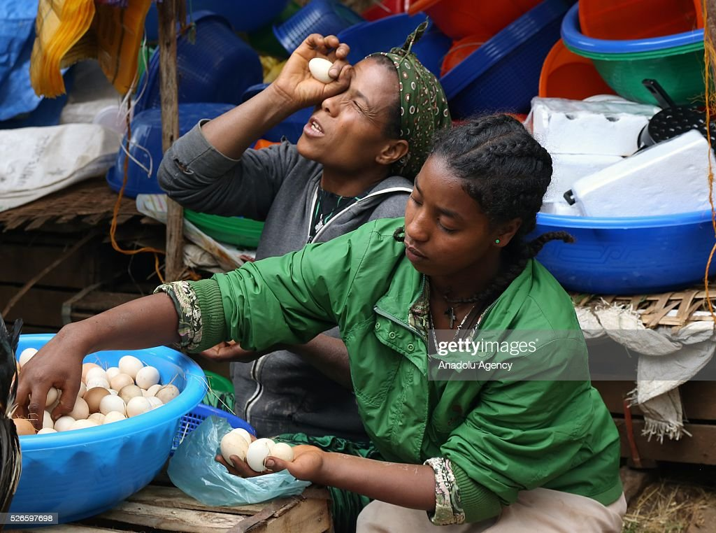 A woman checks an egg as the Ethiopian Orthodox Christians arrive at Sholla livestock market to shopping during the Holy Saturday ahead the Easter in Addis Ababa, Ethiopia on April 30, 2016. Ethiopian Orthodoxes, who has been fasting without eating any food of animal origin last 55 days, buy bovines, sheep and goats ahead of the Easter will be celebrated on tomorrow.