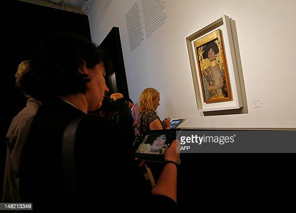 A woman checks an iPad with information on the painting 'Judith' by Austrian artist Gustav Klimt at the Belvedere Palace in Vienna on July 12 2012...