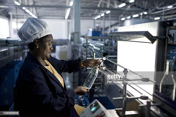 A woman checks bottles of mineral rich sparkling water as it is made in this factory who was established 80 years ago in Sekele locality near a hot...
