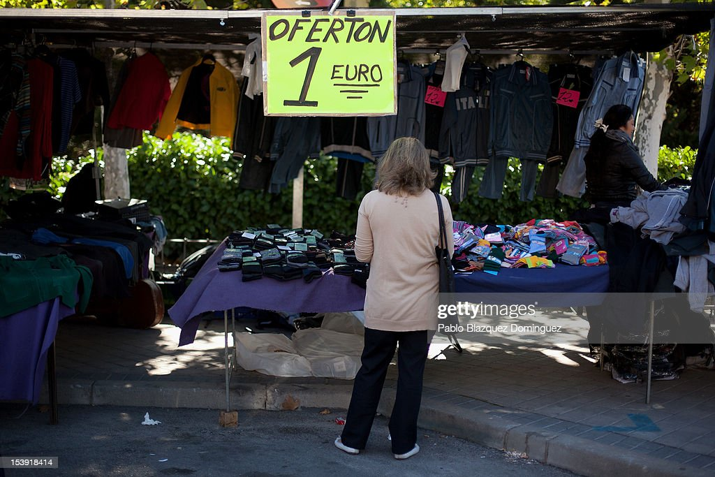 A woman checks clothes for the price of 1 Euro at a street market on October 11, 2012 in Madrid, Spain. Ratings agency Standard & Poor's has cut Spain's credit rating from BBB+ down to BBB-. The Spanish government has already introduced spending cuts and tax rises in an attempt to ease their debt and reduce their high unemployment levels. Spanish Economy Minister Luis de Guindos maintains that his country will not need to ask for a bailout.
