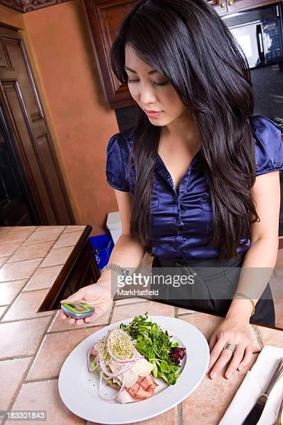 Woman Checks Her Blood Sugar In Modern Kitchen