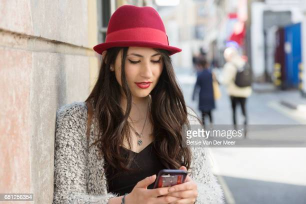 Woman checks her mobile phone messages, while waiting in urban street.