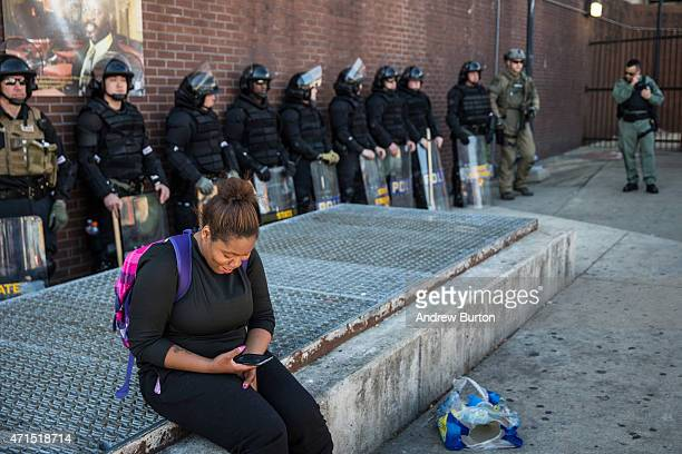 A woman checks her phone while police officers monitor the situation near a CVS pharmacy that was looted and burned by rioters on Monday after the...