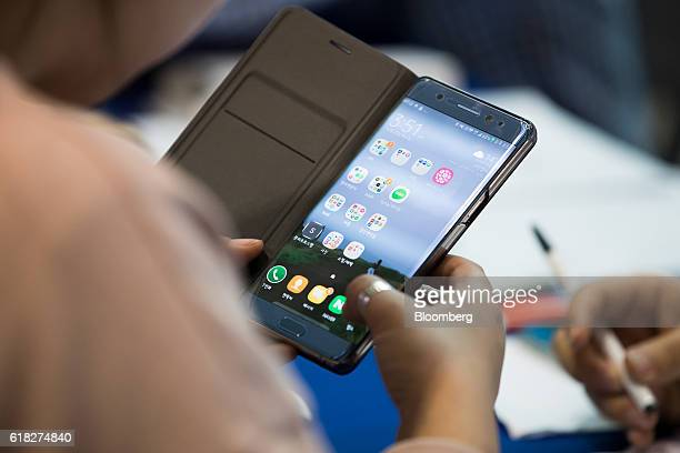 A woman checks her Samsung Electronics Co Galaxy Note 7 smartphone at a Samsung kiosk providing rental phones for users of the Note 7 at Incheon...