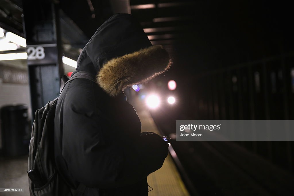 A woman checks her smart phone while awaiting a downtown subway on January 29, 2014 in New York City. Temperatures in New York City edged up over 20 degrees Wednesday as a cold wave continued to grip the country.