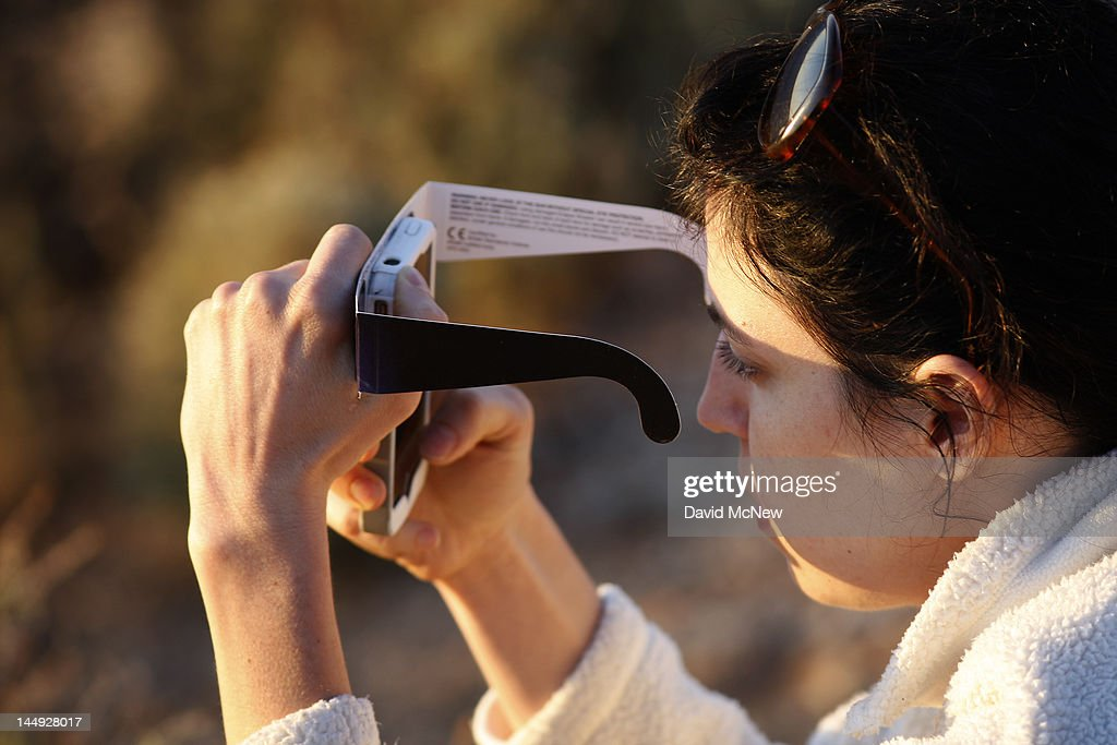 A woman checks her smart phone while watching the first annular eclipse seen in the U.S. since 1994 with special glasses to protect her eyes on May 20, 2012 in Grand Canyon National Park, Arizona. Differing from a total solar eclipse, the moon in an annular eclipse appears too small to cover the sun completely, leaving a ring of fire effect around the moon. The eclipse is casting a shallow path crossing the West from west Texas to Oregon then arcing across the northern Pacific Ocean to Tokyo, Japan.
