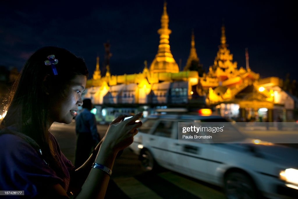 A woman checks her text messages on her phone,as the millennia-old Sule Pagoda stands behind on November 30, 2012 in downtown Yangon, Myanmar. Business opportunities are expanding in the Southeast Asian country as it emerges from financial isolation. Import restrictions have been eased resulting in many new cars seen on the streets.