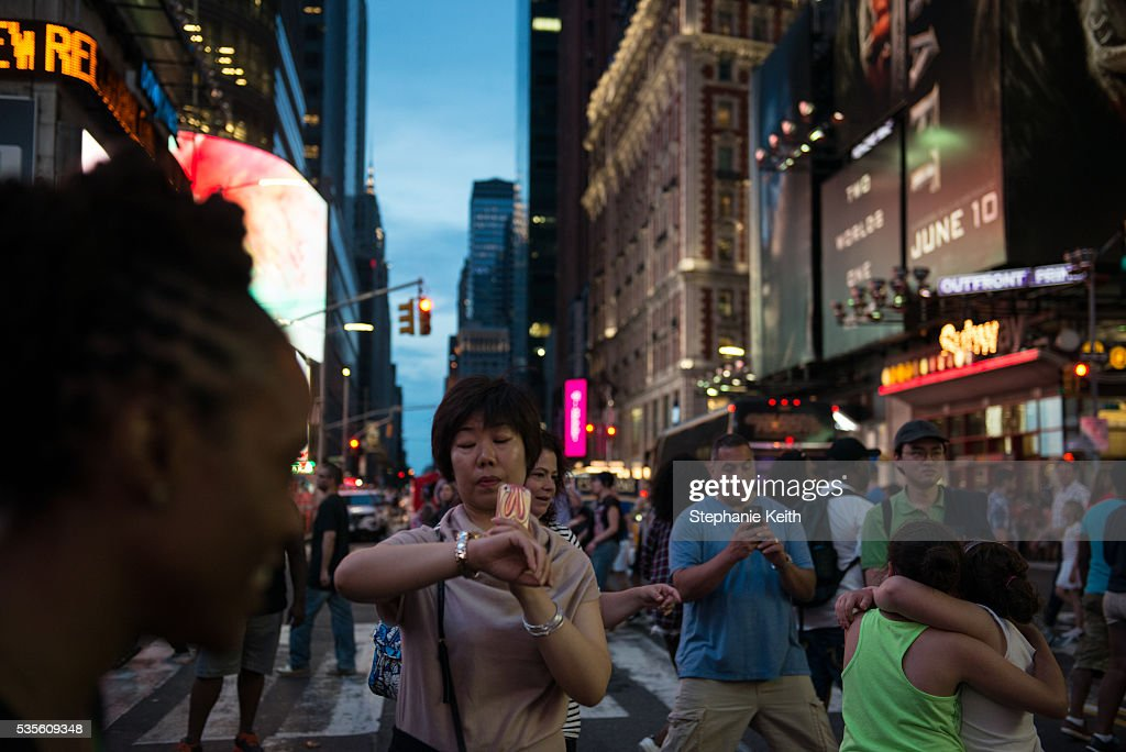 A woman checks her watch while waiting to take a photo of Manhattanhenge, which was not visible due to clouds, on May 29, 2016 in New York City. Manhattanhenge, an event that happens twice a year, occurs when the setting sun aligns with the east-west streets of Manhattan.