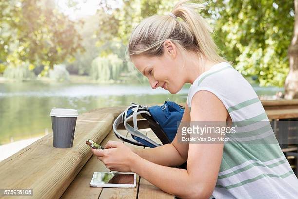 Woman checks mobile device in park cafe