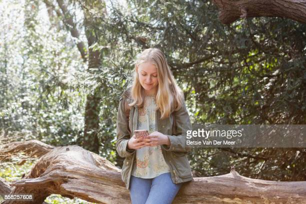 Woman checks mobile phone, sitting on treetrunk in forest.