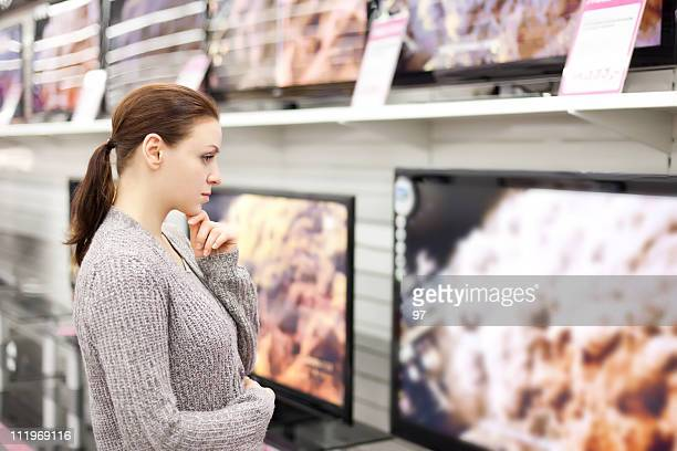 Woman checks out televisions while browsing in Walmart