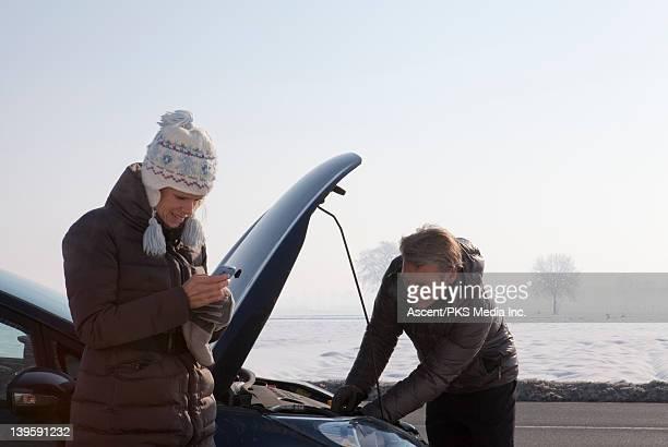 Woman checks phone while man works on car