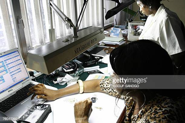 A woman checks raw diamonds 10 August 2007 at Gold and Diamond department of Sierra Leone Central Bank in Freetown The first Sierra Leonean diamond...