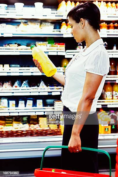 Woman checks supermarket orange juice label carefully