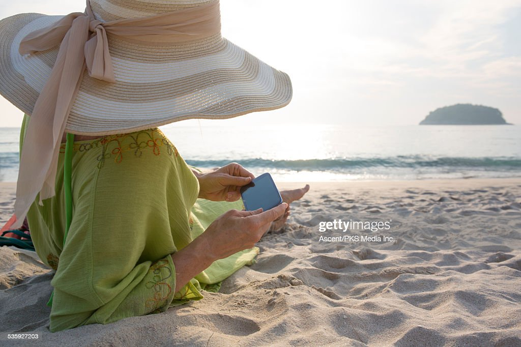 Woman checks text message while lying on beach : Stock Photo