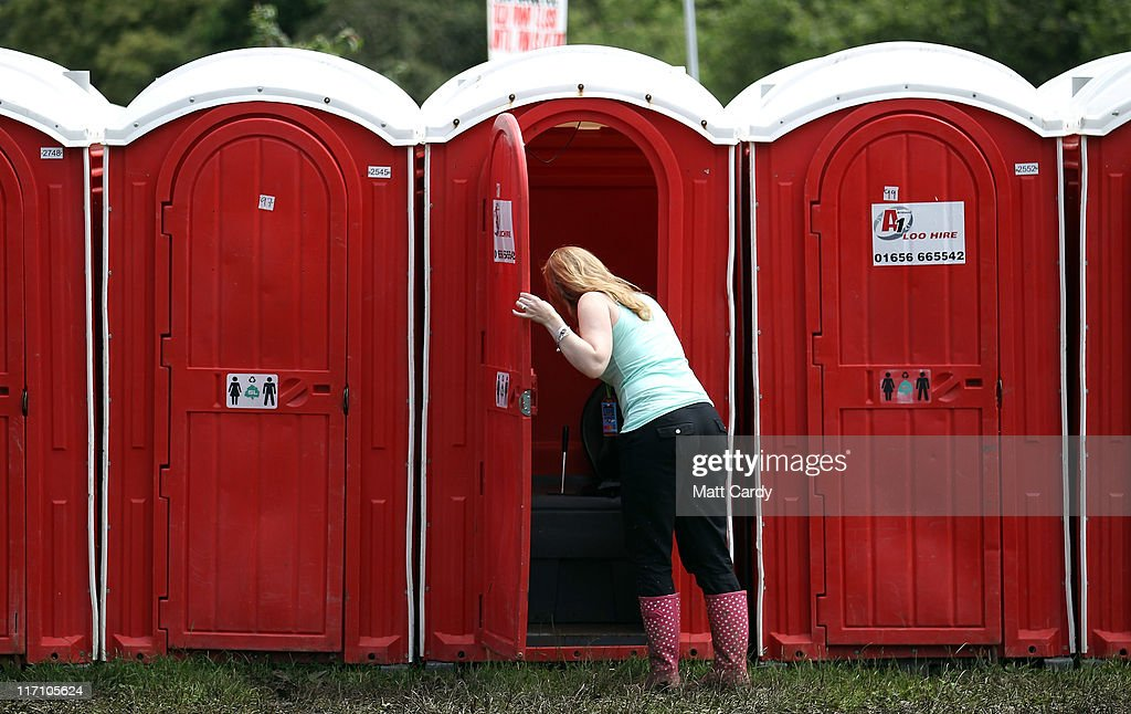 A woman checks the condition of a portable toilet at the Glastonbury Festival site at Worthy Farm Pilton on June 22 2011 in Glastonbury England Heavy...