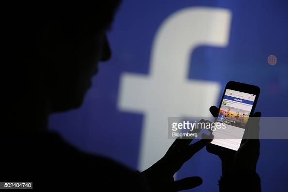 A woman checks the Facebook Inc site on her smartphone whilst standing against an illuminated wall bearing the Facebook Inc logo in this arranged...