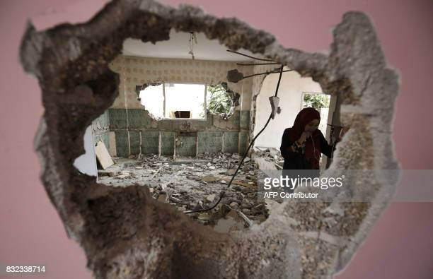 TOPSHOT A woman checks the remains of the house of a Palestinian man who killed three Jewish residents of a nearby Israeli settlement after it was...