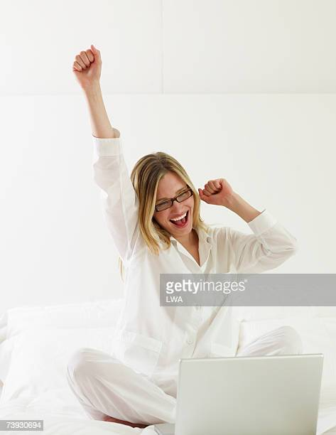 Woman cheering in front of laptop on bed