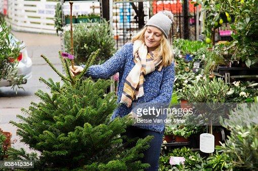 Woman chooses a christmas tree, standing in urban garden center.