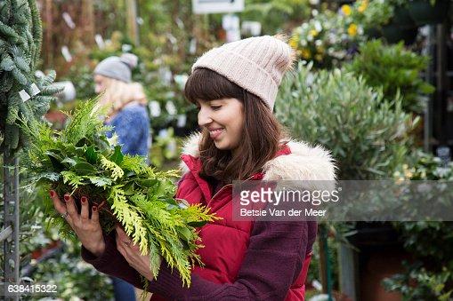 Woman chooses Christmas wreath at urban garden centre.